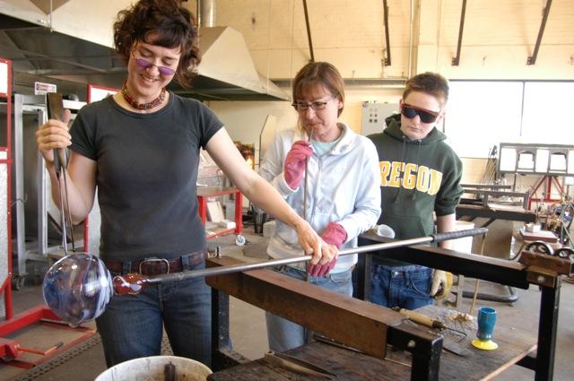 Kelly Howard helps glass blowers blow glass at Jennifer L Sears Glass Art Studio in Lincoln City