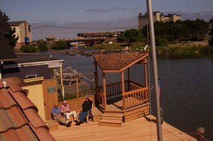 Visiting on the Dunlap Lodge deck in full sight of Devils Lake, D River and the Pacific Ocean; photo by Jan Jackson